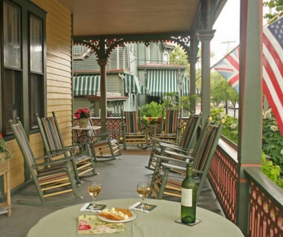 Exterior of The Queen Victoria with rocking chairs, wine, and snacks.