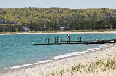 man walking on a dock in lake michigan near glen arbor
