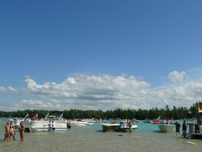 people hanging out in the water at torch lake with their boats