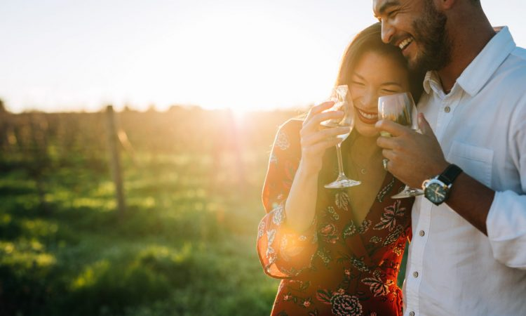 couple laughing and drinking wine outdoors at a bed and breakfast