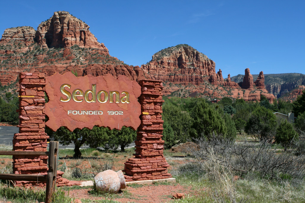 image of red rock formations near sign for sedona