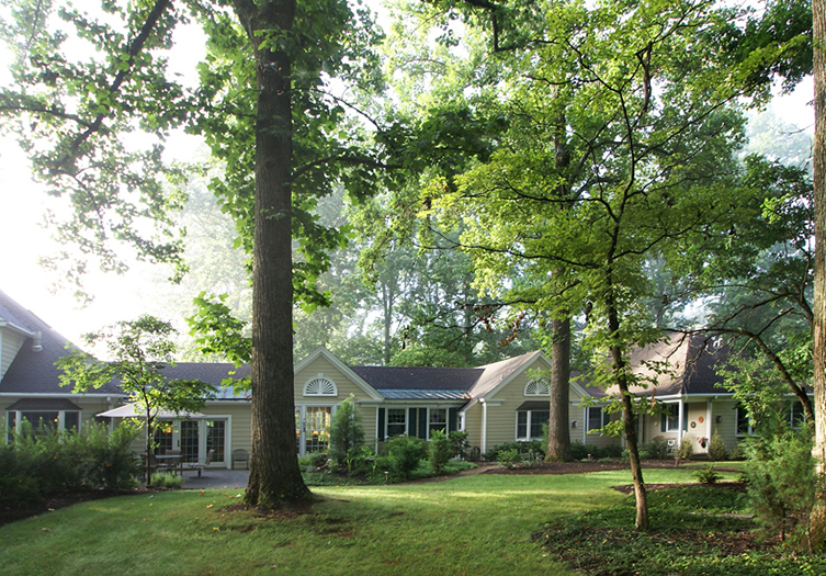 Exterior shot of the back of the Inn, with large trees and grassy areas