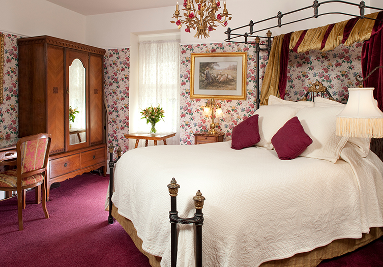 Churchill Bedroom with rose colored carpets pillows and floral wallpaper