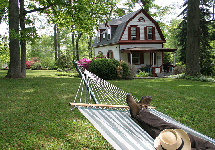 Striped hammock outside Carriage House cottage with barn style roof surrounded by trees and green lawn