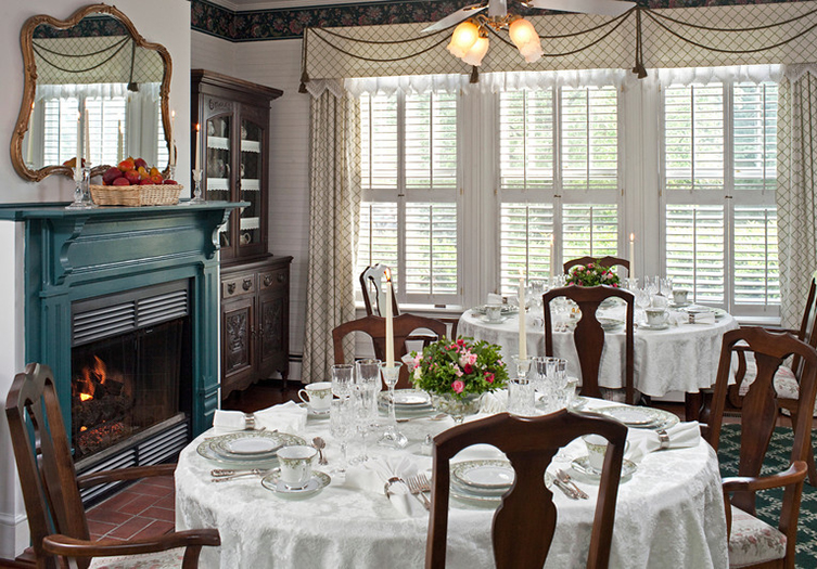 Dining Room with fireplace, seperate tables seating 4 persons, with white linens, fine china and crystal glassware