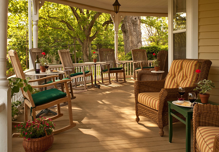 Outside Front Porch with rocking chairs, ratan furniture with green cushions and red potted flowers