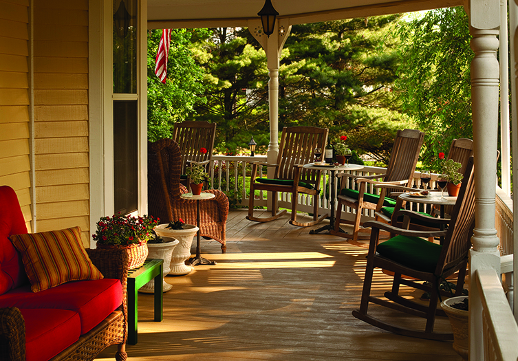 Outside Front Porch with rocking chairs, ratan furniture with red and green cushions