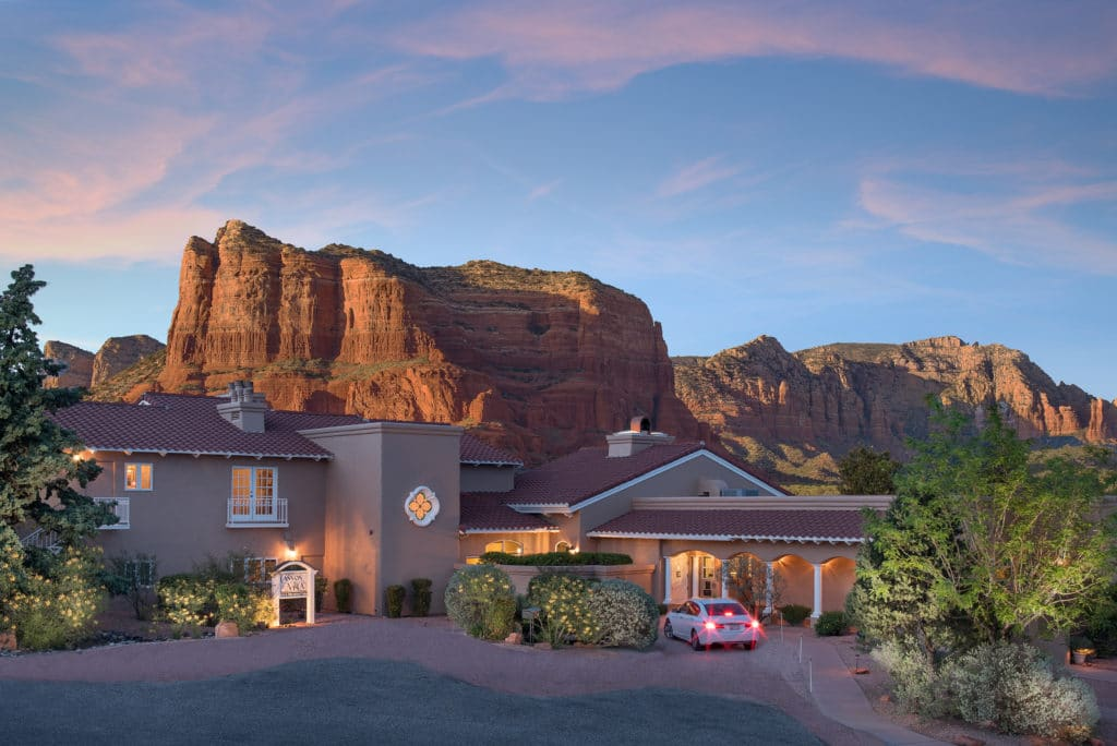 Exterior view of the canyon villa bed and breakfast inn of sedona arizona with views of the beautiful landscapes behind the property