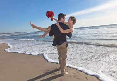 Wedding couple standing in surf in Half Moon Bay