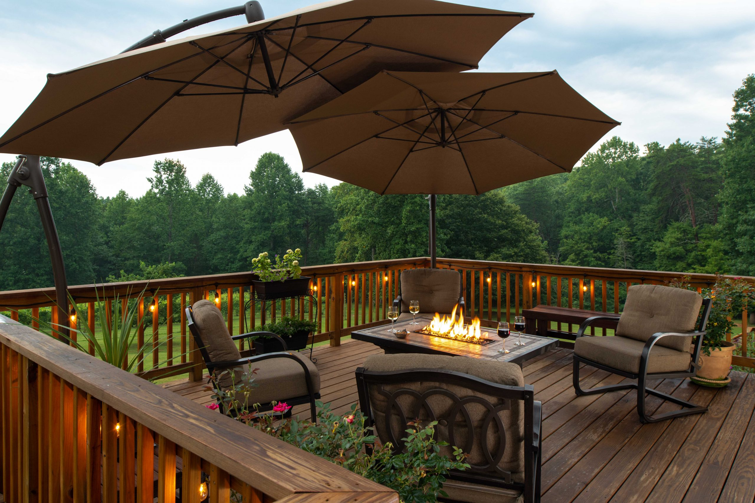 Arcady's main back deck, spacious with cushioned patio furniture and umbrellas and a warm glowing firepit.jpg