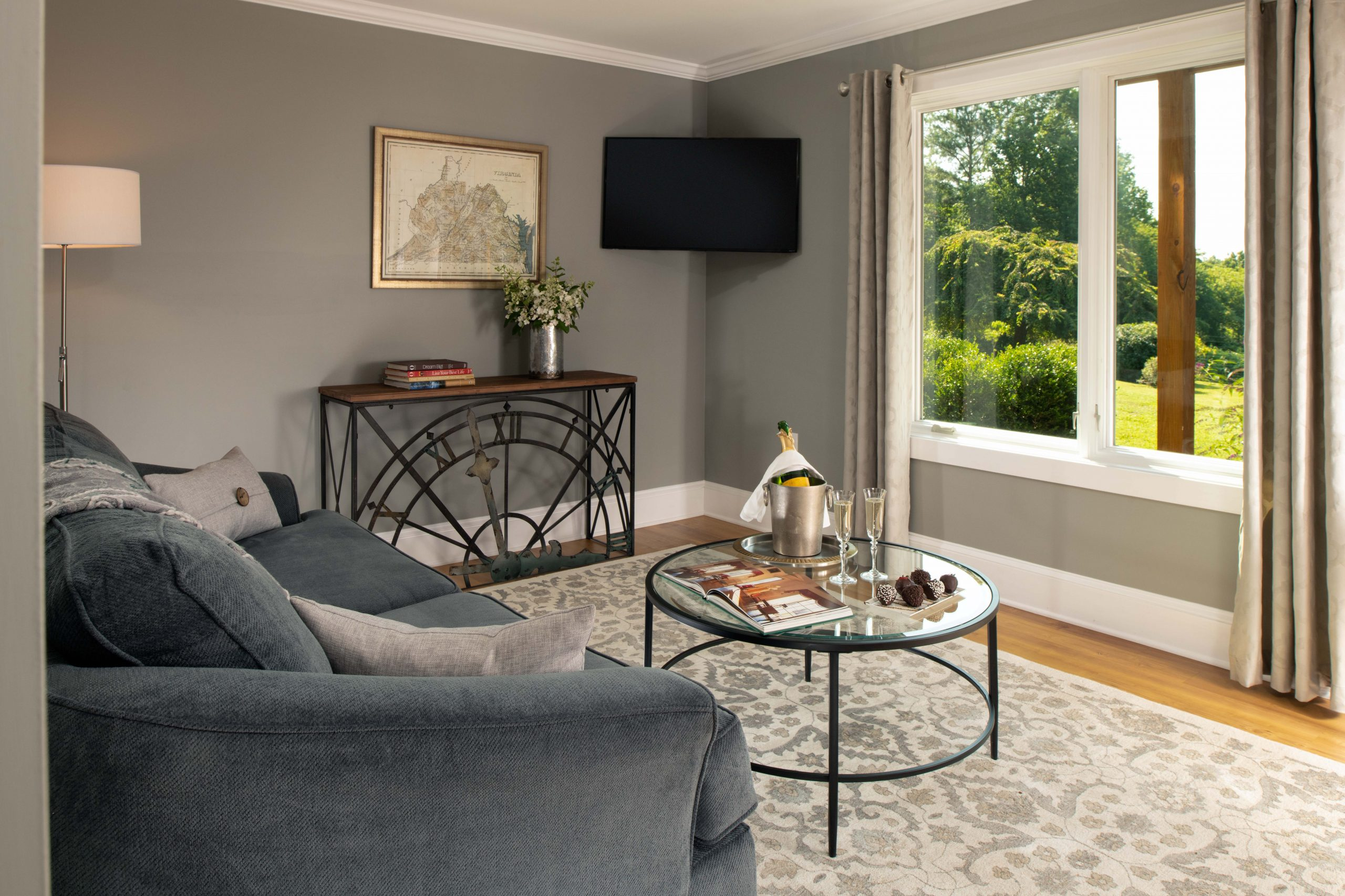 Arcady's Madison Suite sitting room with large windows, light wood floors, area rug, upholstered sofa, tables and TV