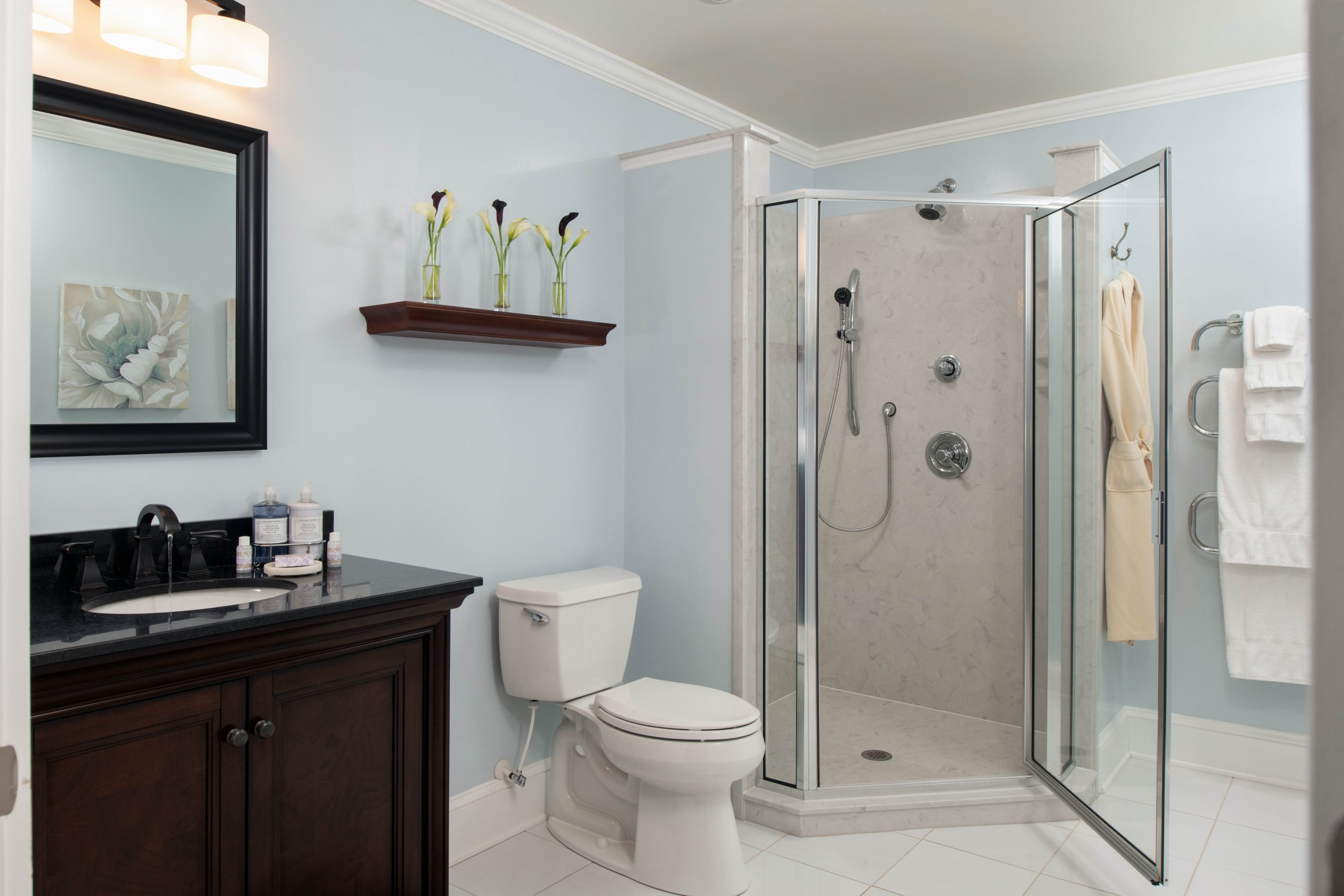 Arcady's Madison Suite bathroom with light blue walls, white tile, walk-in shower, and dark vanity with mirror.jpg