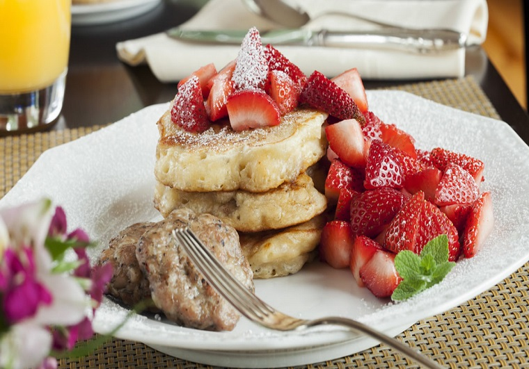 Arcady's breakfast - white plate topped with stack of pancakes, lots of fresh strawberries and sausage patties