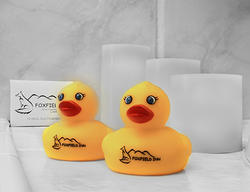 Two rubber duckies, complimentary bath grains and candles