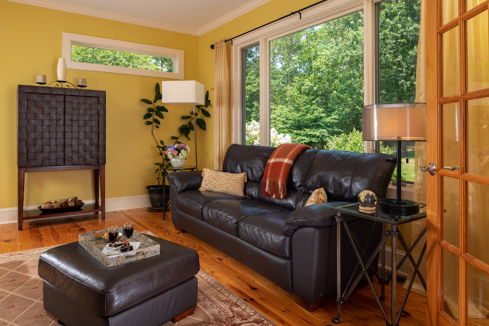 Cozy common Sitting Room with large window, wood floors, and leather furniture
