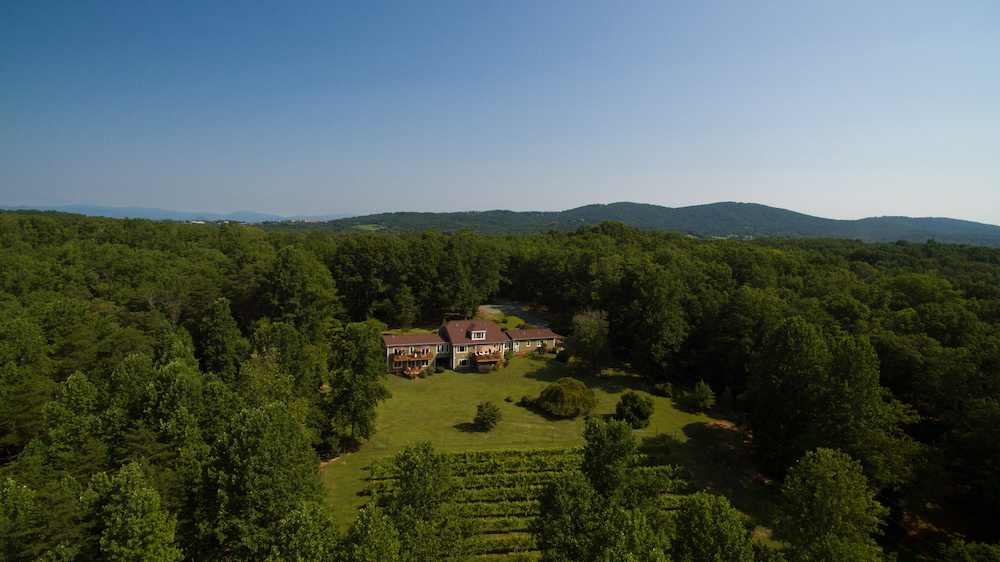Aerial view of B&B surrounded by miles of hilly lush green trees and clear blue skies