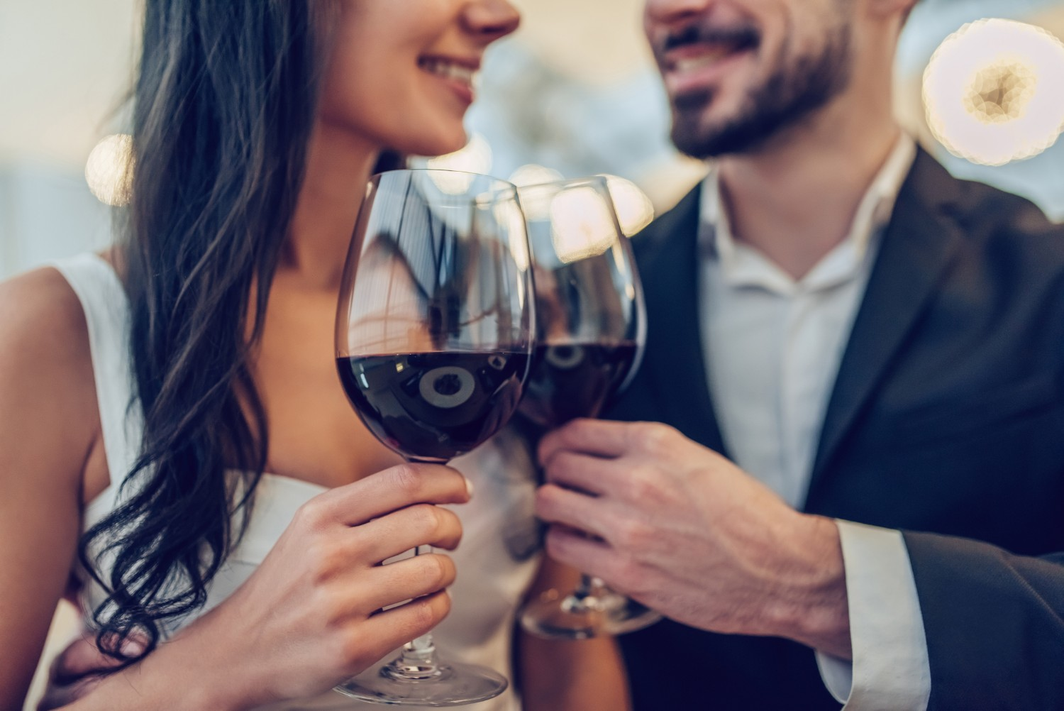 Cropped image of loving couple is spending time together in modern restaurant. Attractive young woman in dress and handsome man in suit are having romantic dinner. Celebrating Saint Valentine's Day. (Cropped image of loving couple is spending time tog