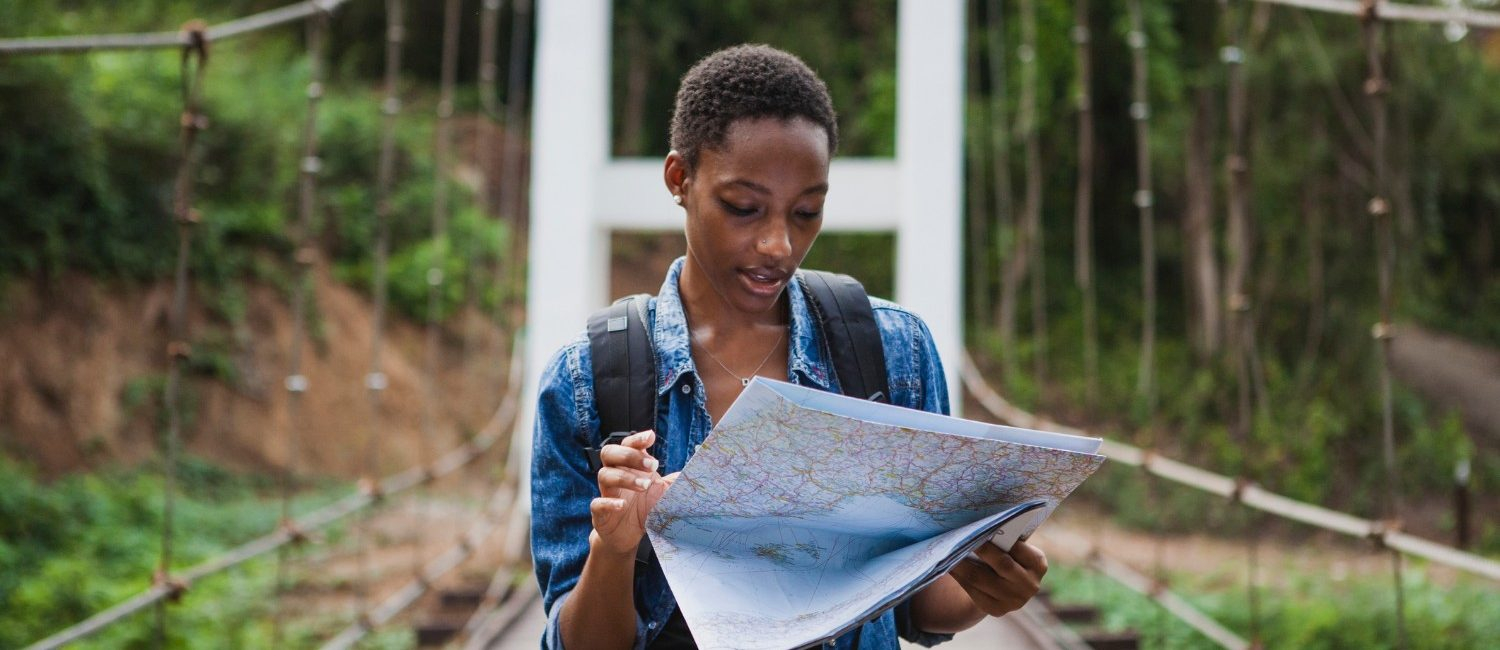 woman looking over a map on a bridge while exploring nature at a top travel destination