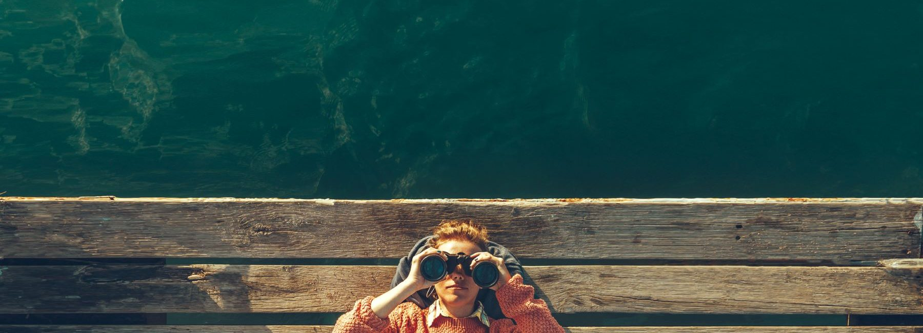 Girl with Binoculars on pier by the sea