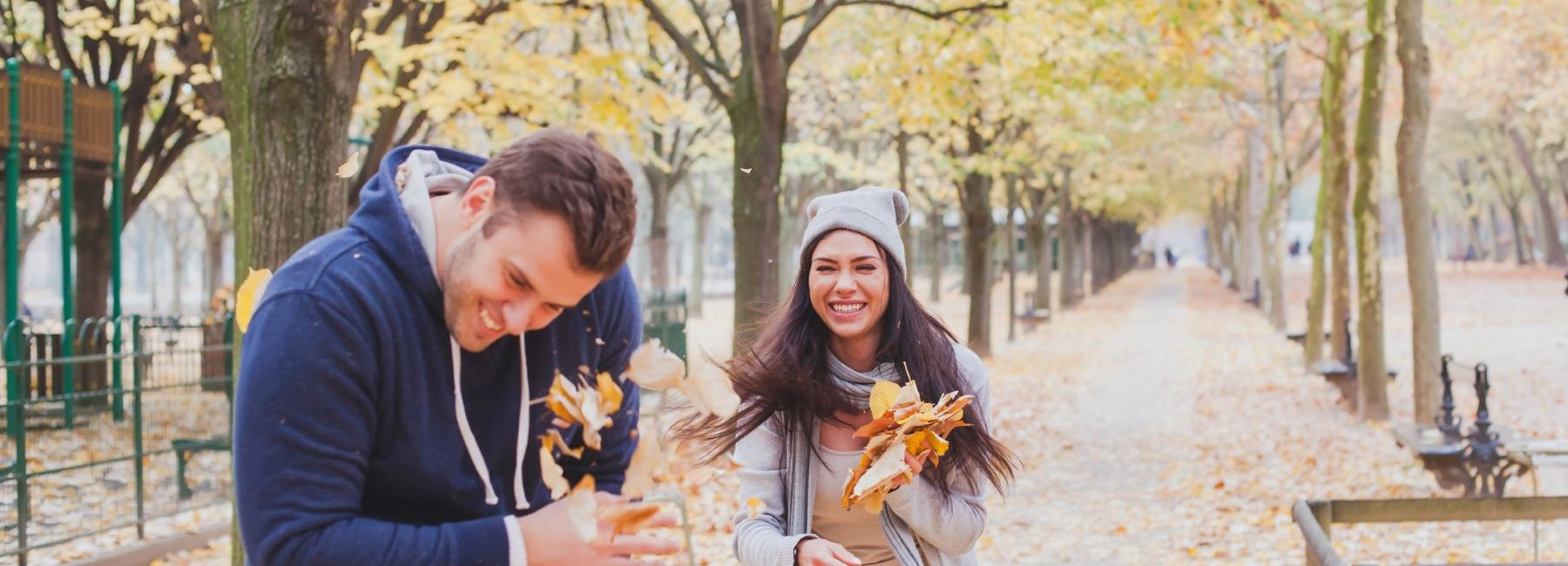 Couple in the Fall throwing leaves having fun