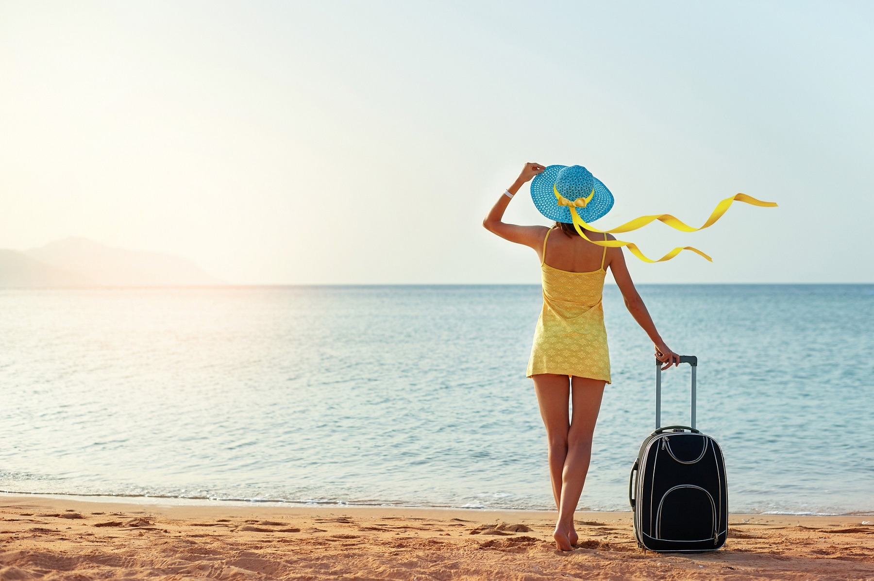 woman standing on the beach with a suitcase